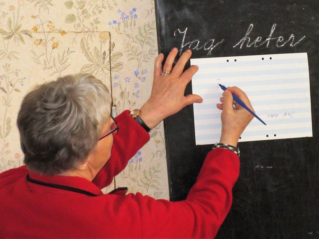 """""""Fröken"""" visar hur man skriver med bläckpenna."""