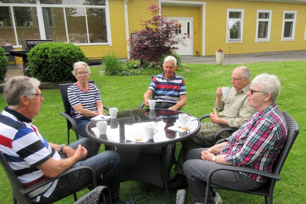 Mätta och belåtna bestämde dessa personer avnjuta sitt kaffe utomhus. De första regndropparna syns på bordskivan. Sedan öppnade himmeln sig i ett riktigt skyfall